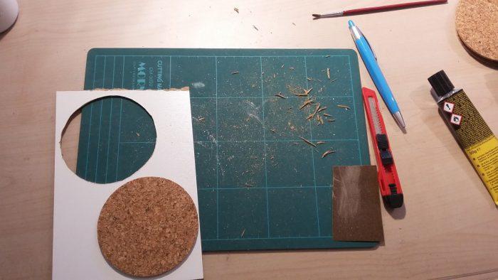 Foto von dem benötigten Material für das DIY Untersetzer Upcycling: MDF-Platte, Kork, Cutter, Schneideunterlage, Kuli, Pinsel, weiße Farbe, Kleber