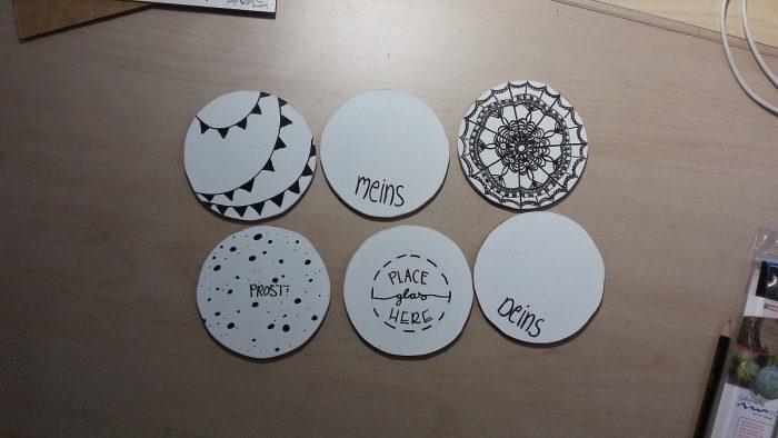 Foto von oben, mit den sechs fertig designten Untersetzern: mit Wimpelkette, Doodle-Bild und Handlettering